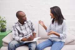 Woman sitting while therapist looking at her Stock Photography