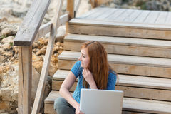 Woman sitting thinking with her laptop Royalty Free Stock Images