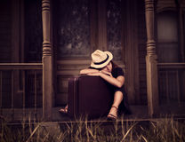 Woman sitting on threshold of old house. Portrate of young woman in white hat with retro suitcase is sitting on threshold of old house Royalty Free Stock Photos