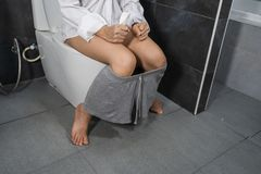 Woman sitting on toilet royalty free stock photography