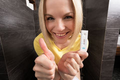 Woman is sitting on the toilet and holding a positive pregnancy test. A beautiful young blonde woman sits in the bathroom and holds a positive pregnancy test Stock Photos