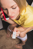 Woman is sitting on the toilet and holding a positive pregnancy test and mobile phone. A beautiful young blonde woman sits in the bathroom and holds a positive Royalty Free Stock Images