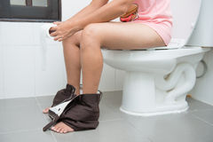 Woman sitting on a toilet. Restroom Stock Photos