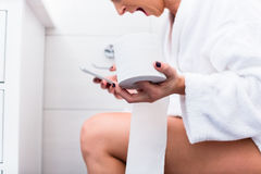 Woman sitting on toilet writing text message on cell phone Royalty Free Stock Photo
