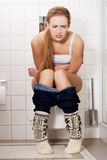 Woman sitting on a toilet Stock Images