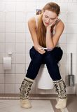 Woman sitting on a toilet Stock Photography