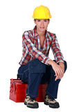 Woman sitting on a toolbox Royalty Free Stock Image