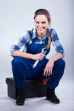 Woman sitting on toolbox. Resting woman sitting on toolbox and holding wrench Stock Images
