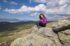 Woman sitting on top of mountain typing in tablet Stock Photography