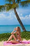 Woman sitting on a towel at the beach Royalty Free Stock Photos