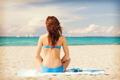 Woman sitting on a towel Stock Photography