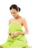 Woman sitting in towel, making heart shape Royalty Free Stock Photo