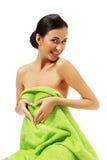 Woman sitting in towel, making heart shape Stock Photo
