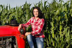 Woman sitting on tractor in field Stock Images