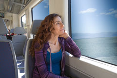 Woman sitting in train looking through the window Royalty Free Stock Photos