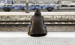 Woman sitting in a train station Stock Images