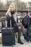 Woman sitting at train station with her suitcase Stock Photography