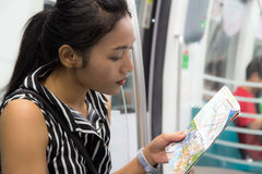Woman sitting in a train. And is studying the route map Royalty Free Stock Photography