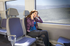 Woman sitting in train talking on mobile Royalty Free Stock Photo