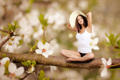 Woman sitting on tree Royalty Free Stock Photos