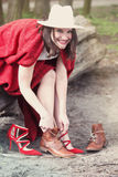 Woman sitting on tree and changing her shoes. Young woman sitting on tree and changing her high heels for boots Royalty Free Stock Photo