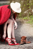 Woman sitting on tree and changing her shoes. Young woman sitting on tree and changing her high heels for boots Stock Photos