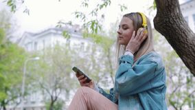 Woman sitting on a tree in the Park and listening to music. Woman sitting on a tree in the Park and listening to music stock video footage