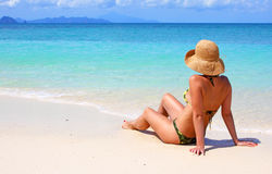 Woman sitting on a tropical beach Royalty Free Stock Photo