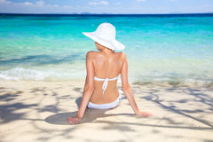 Woman sitting at tropical sea shore. Stock Image