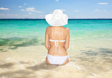 Woman sitting at tropical sea shore. Royalty Free Stock Photography