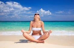 Woman sitting at tropical sea shore. Royalty Free Stock Photos