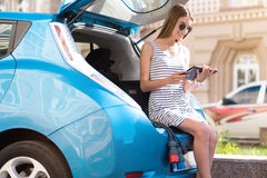Woman sitting on trunk with tablet Stock Photography