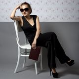 Woman sitting on two chairs Stock Photos