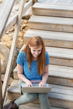 Woman sitting typing on her laptop Stock Photos
