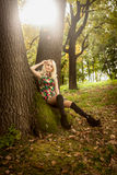 Woman sitting under big old oak at forest Royalty Free Stock Image