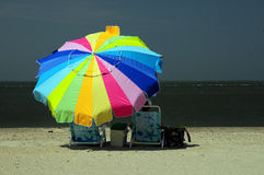 Woman sitting under colorful umbrella Royalty Free Stock Photo