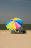 Woman sitting under colorful umbrella Royalty Free Stock Photos