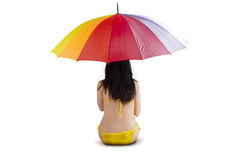 Woman sitting under colorful umbrella Stock Photo