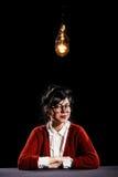 Woman sitting under the light bulb Stock Photos