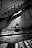 Woman sitting under metal staircase in beam of light Stock Photo