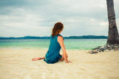 Woman sitting under palm tree on beach Stock Image