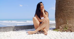 Woman Sitting Under Palm Tree at Tropical Beach. Woman with Long Dark Hair Sitting Cross Legged on Sand at Base of Palm Tree Trunk Overlooking Beach and Blue stock video footage