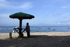 Woman sitting under Parasol on white sand beach. silhouettes. Laiya, San Juan, Batangas, Philippines - May 28, 2017: woman sitting under Parasol on white sand Royalty Free Stock Photos