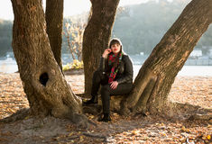 Woman sitting under tree at autumn park next to river Royalty Free Stock Photos