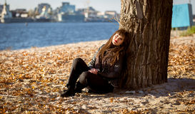 Woman sitting under tree on beach at sunny day Royalty Free Stock Photos