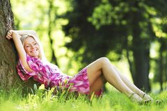 Woman sitting under tree Royalty Free Stock Images