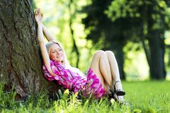 Woman sitting under tree Stock Images