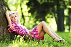 Woman sitting under tree Stock Photo