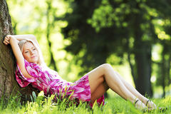 Woman sitting under tree Stock Image