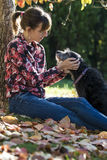 Woman sitting under a tree fondling her dog Stock Photography